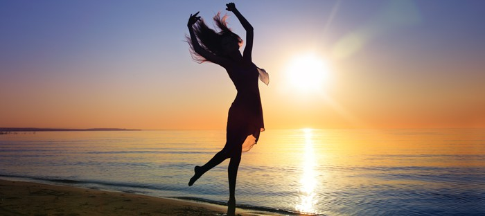 Silhouette of the woman dancing at the beach during beautiful sunset. Natural light and darkness. Artistic vivid colors added