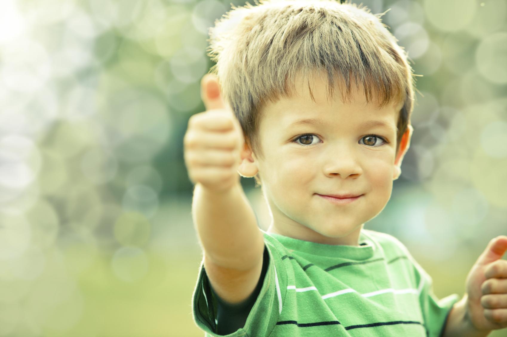 happy smiling kid outdoor doing OK portrait green tone